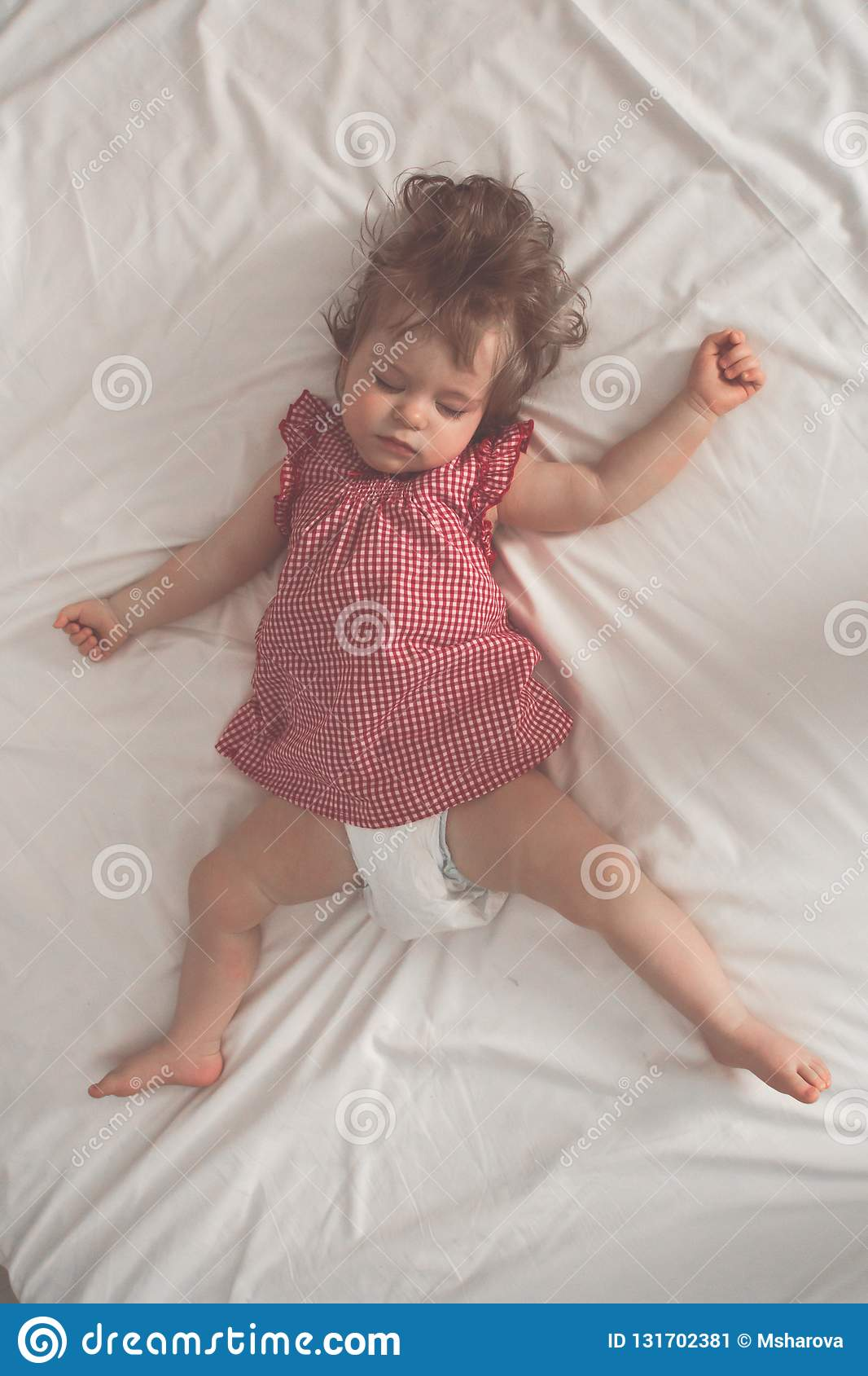 Baby girl sleeping on back with open arms and without pacifier in a bed with white sheets. Peaceful sleeping in a bright