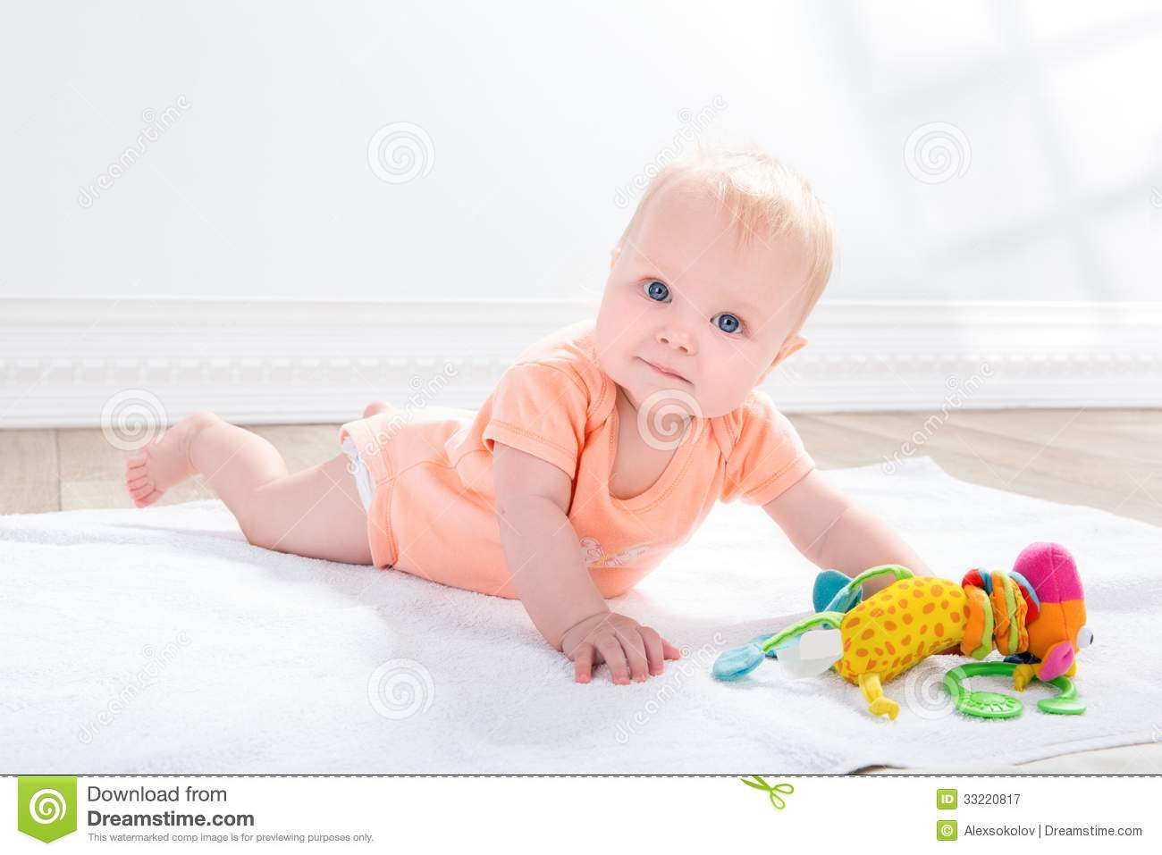 Baby Floor Toys : Baby girl with toy lying on the floor stock image