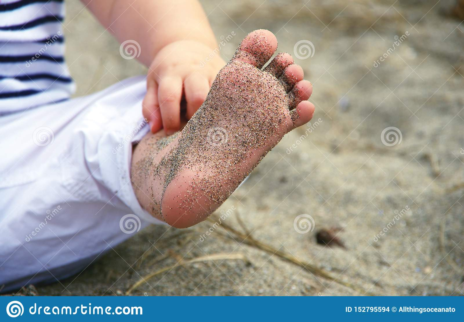 Baby girl wearing striped shirt and white pants, showing her sand-covered foot at a beach in Vancouver, BC Canada.