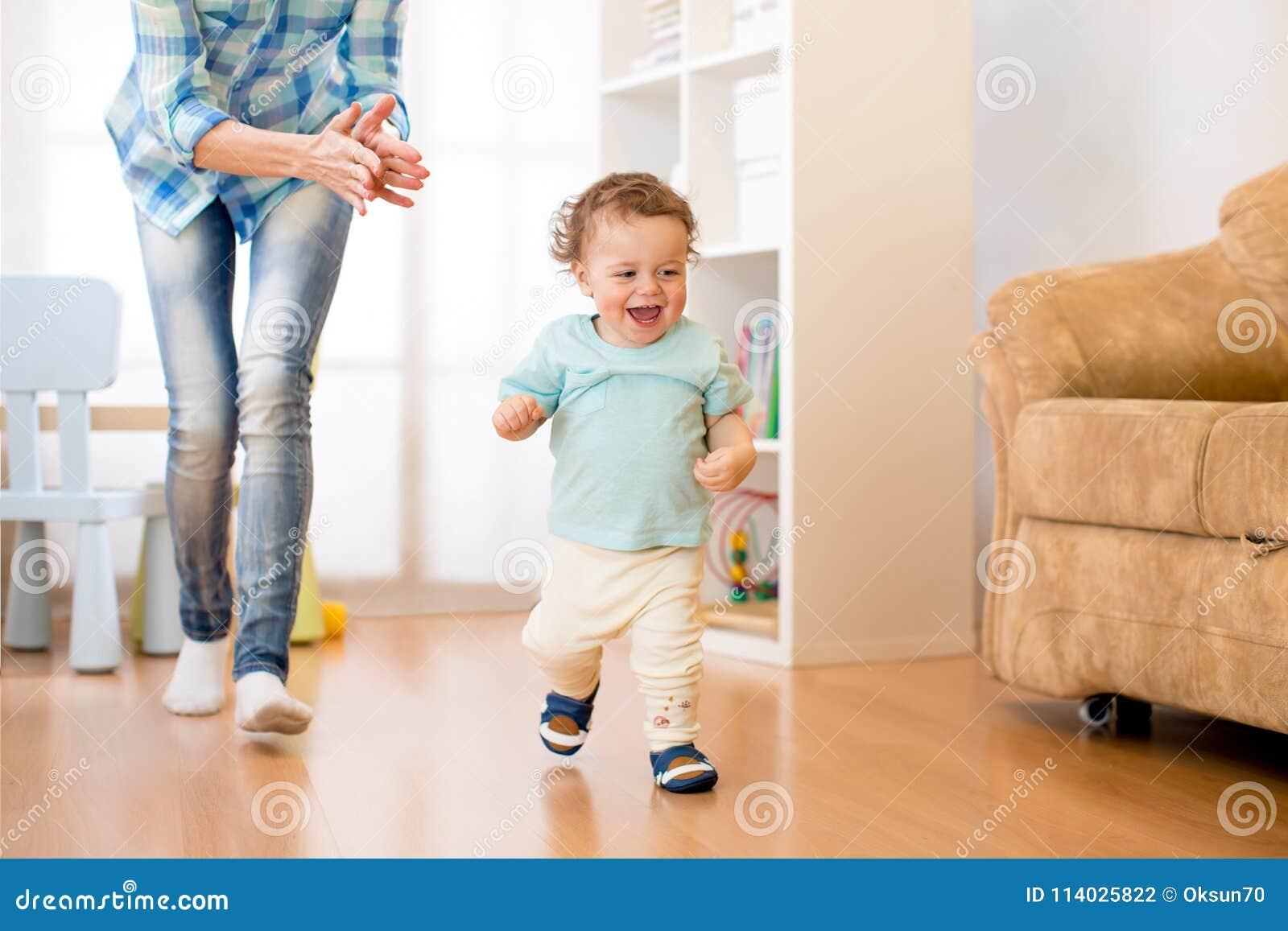 Baby haben einen Spaß, der im Wohnzimmer mit seiner Mutter läuft