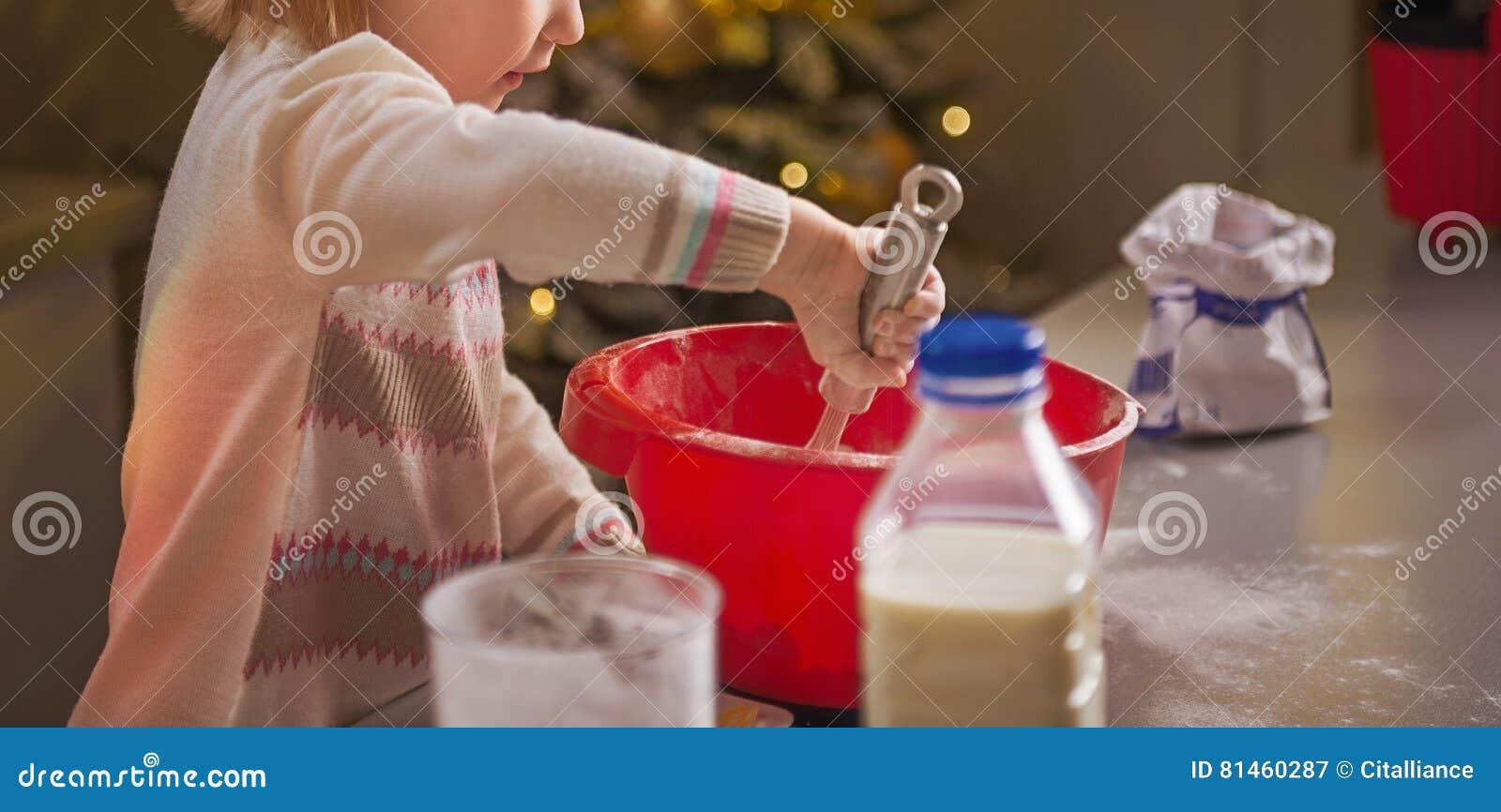 Baby het kneden deeg in Kerstmis verfraaide keuken