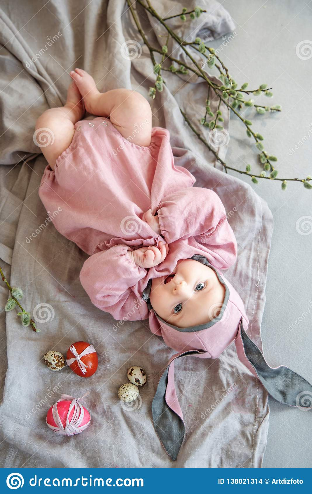 Baby het liggen op linnendeken en het dragen van een hoed in de vorm van een Paashaas met eierenwilg vertakken zich en Pasen-past