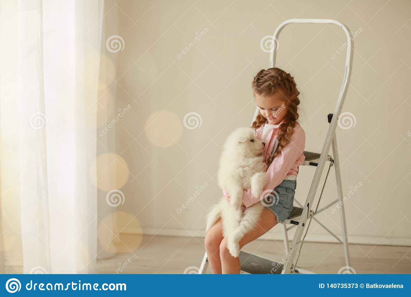 Baby Hugs the white fluffy puppy. Kids