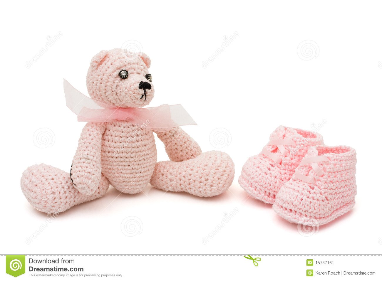 Handmade pink baby booties and teddy bear isolated on a white
