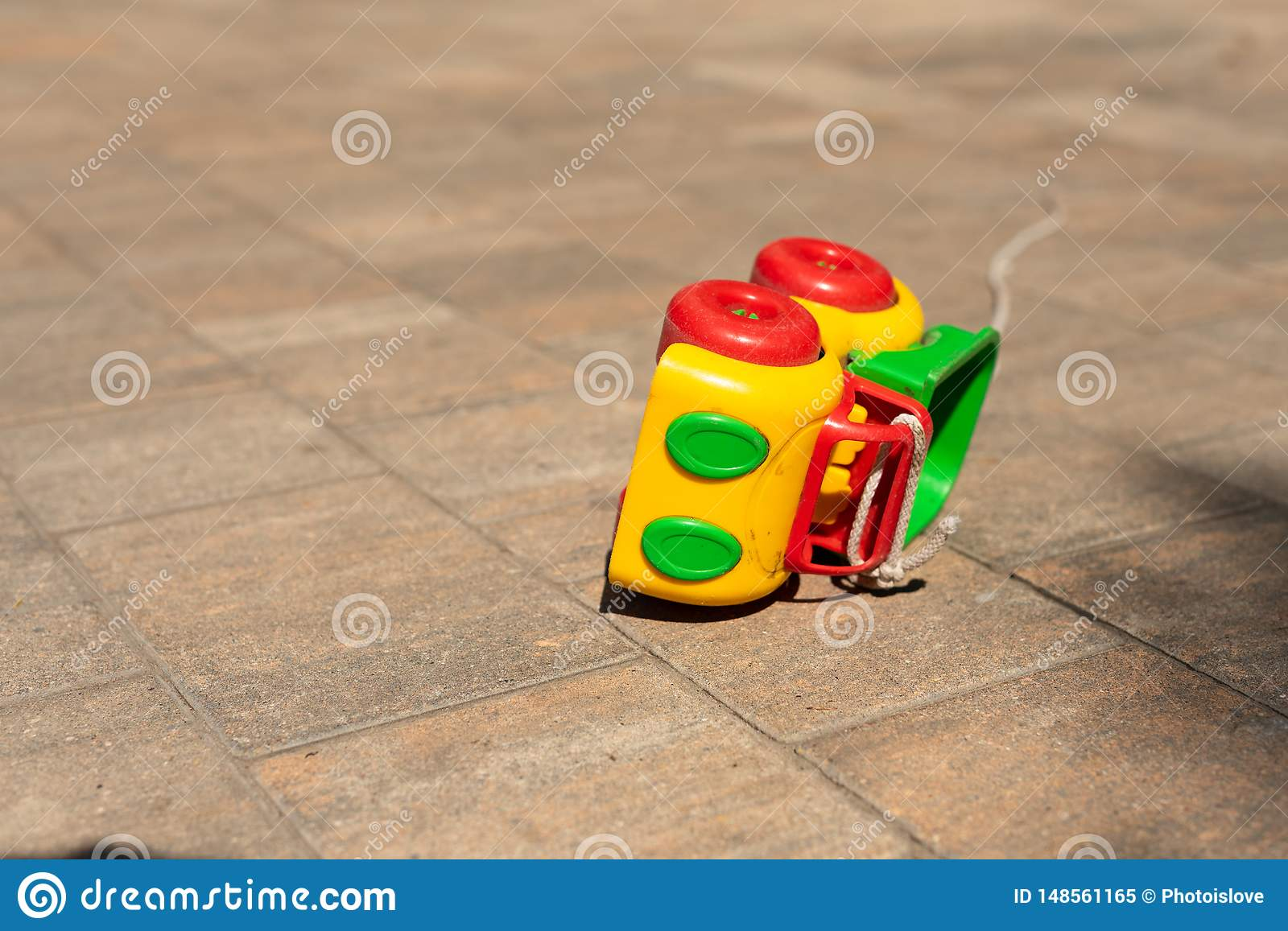 Baby kids toy background: toy colored car knocked over on the paving stone.