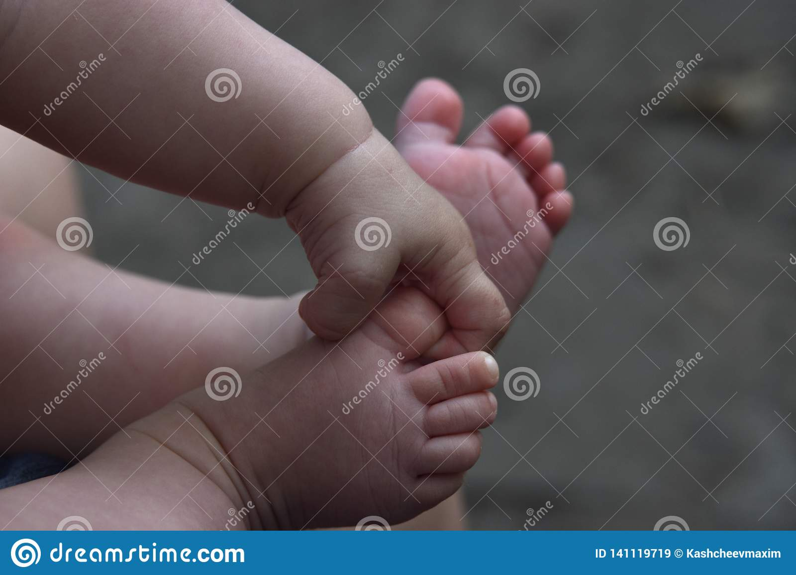 Baby legs and handles close up on gray background