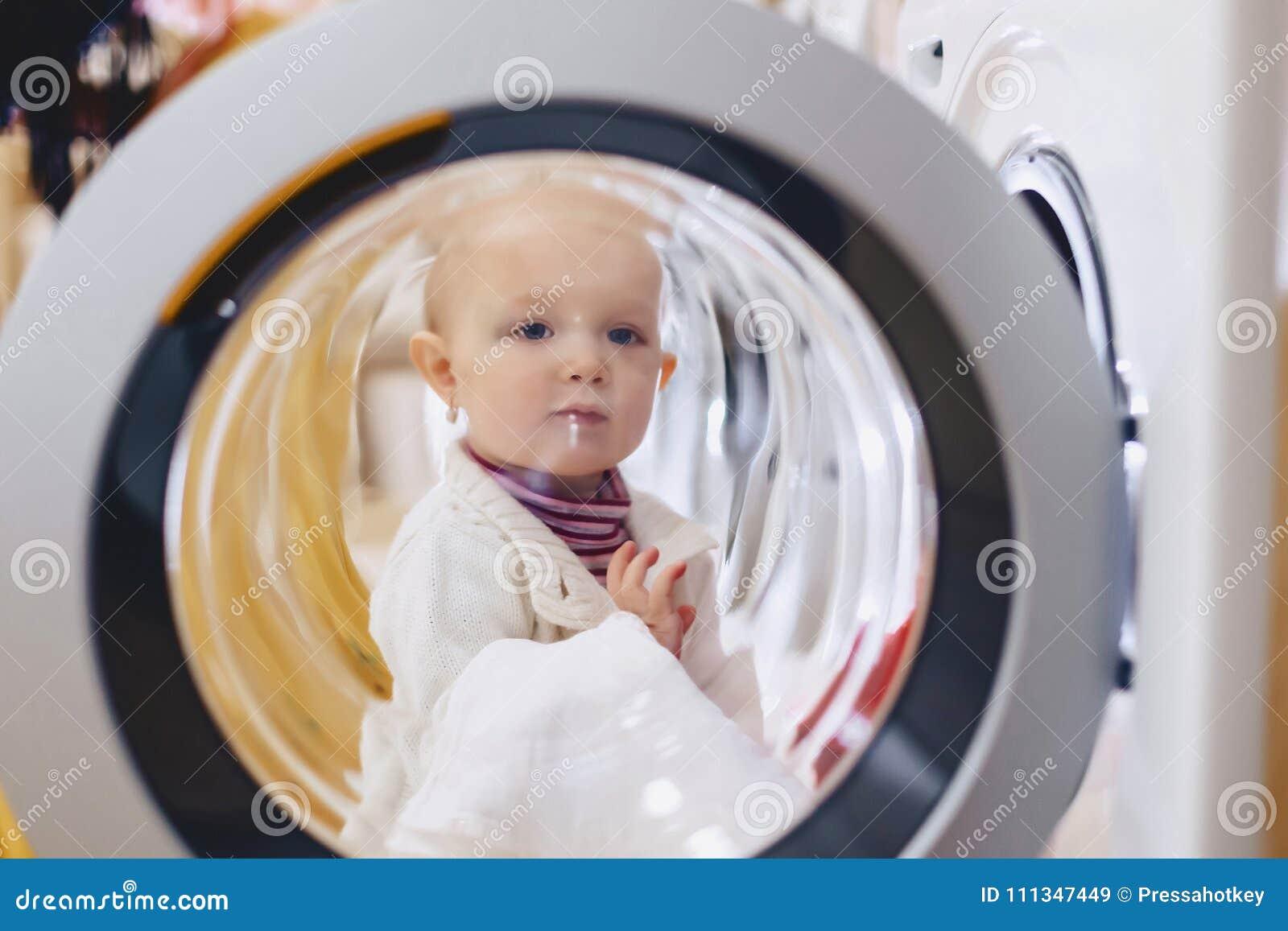 The baby looks through the window of the washing machine