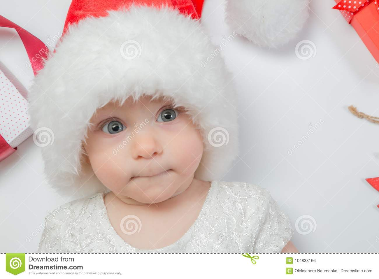 bd866d293ee5 Baby lying with presents in santa hat on white background, top view.  Christmas concept