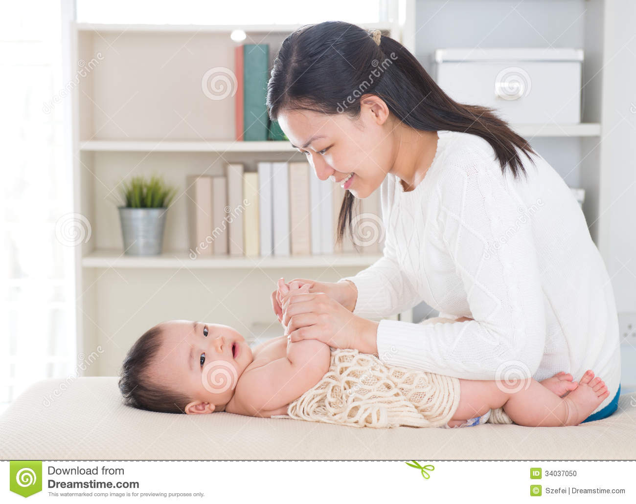 Baby massage. Asian mother massaging baby hands at home.