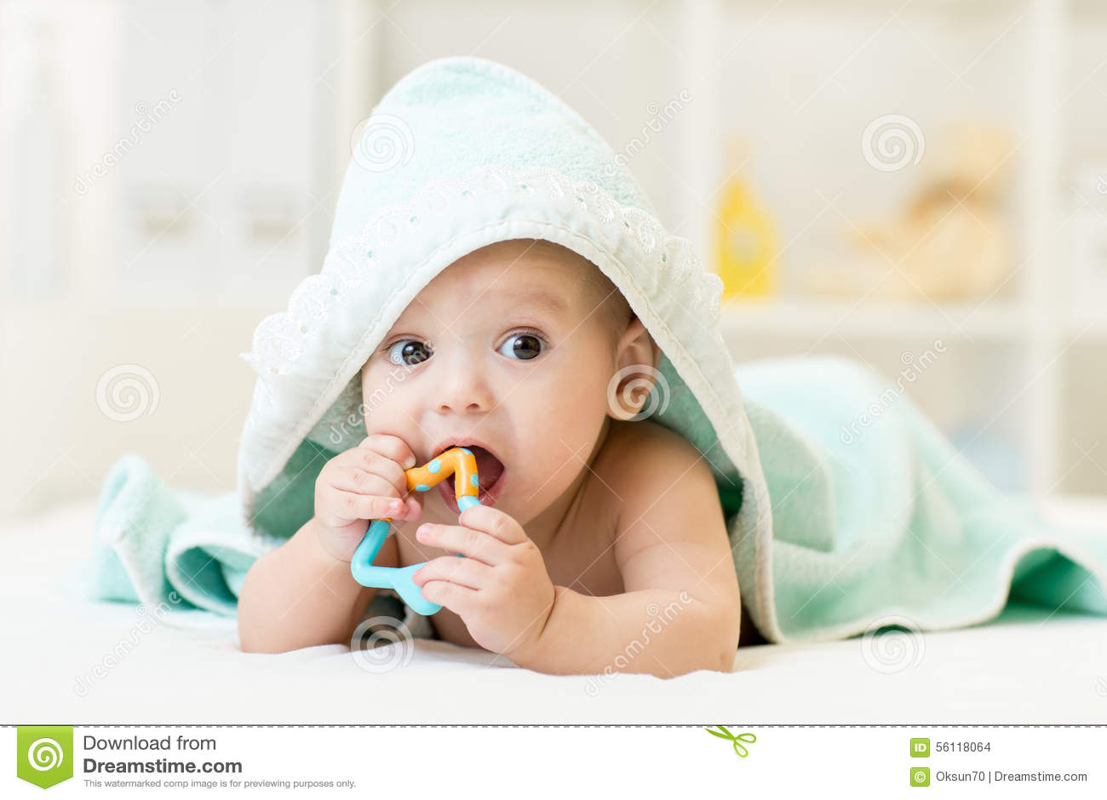Baby met teether in mond onder het baden handdoek bij kinderdagverblijf