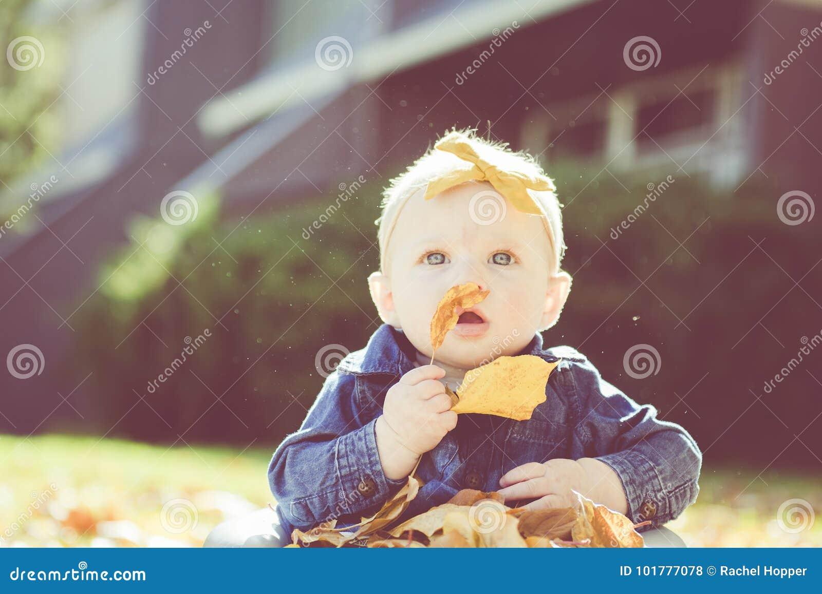 Baby mit Bogen im Kopf, der mit Blättern an einem Fall-Tag spielt