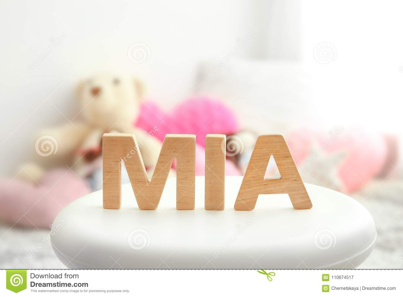Baby name MIA composed of wooden letters on stool.
