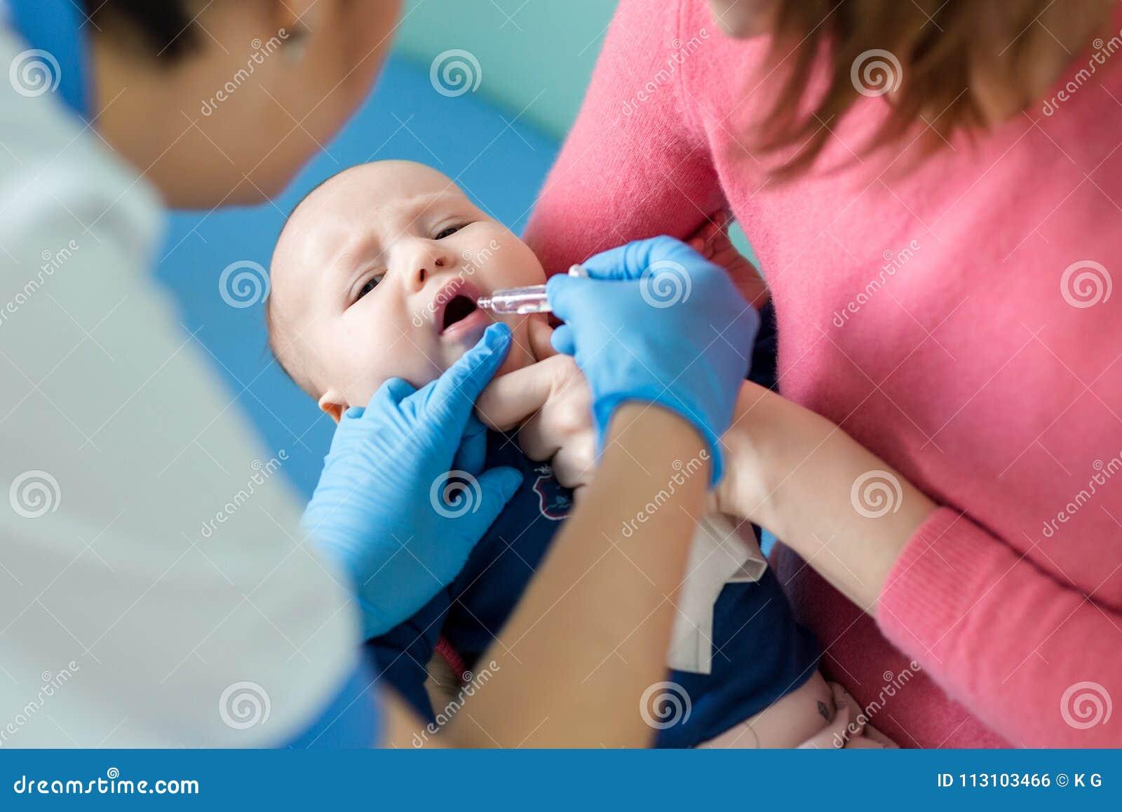 Baby op moedershand bij het ziekenhuis Verpleegster die zuigeling tot mondelinge inenting maken tegen rotavirusbesmetting Kindere