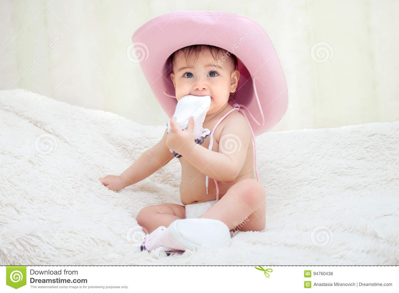 4176980f713e5 Baby In A Pink Cowboy Hat Sitting In Diapers On The Couch Stock ...