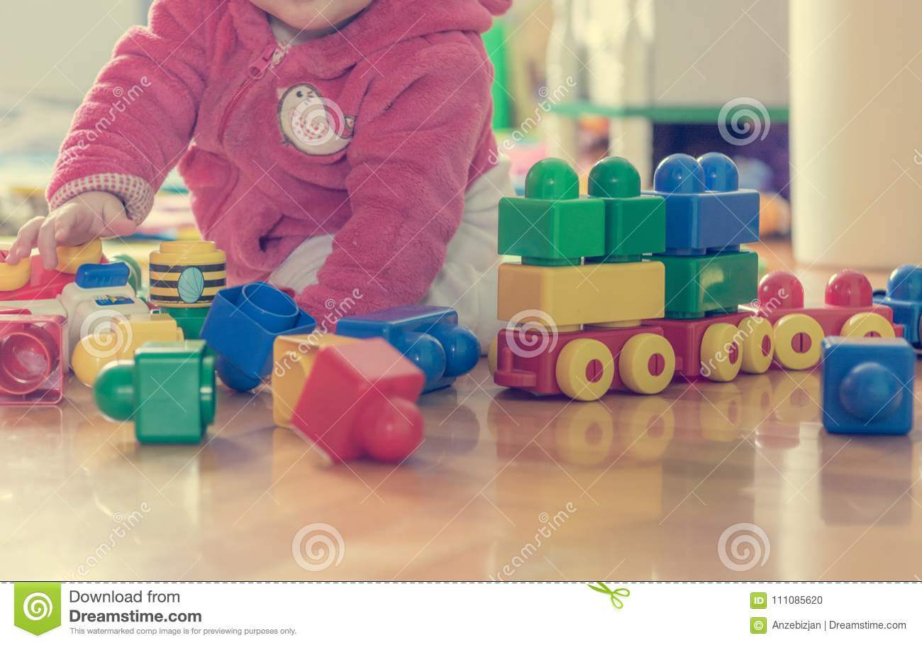Baby Playing With Colorful Bricks On Wooden Floor Stock Photo
