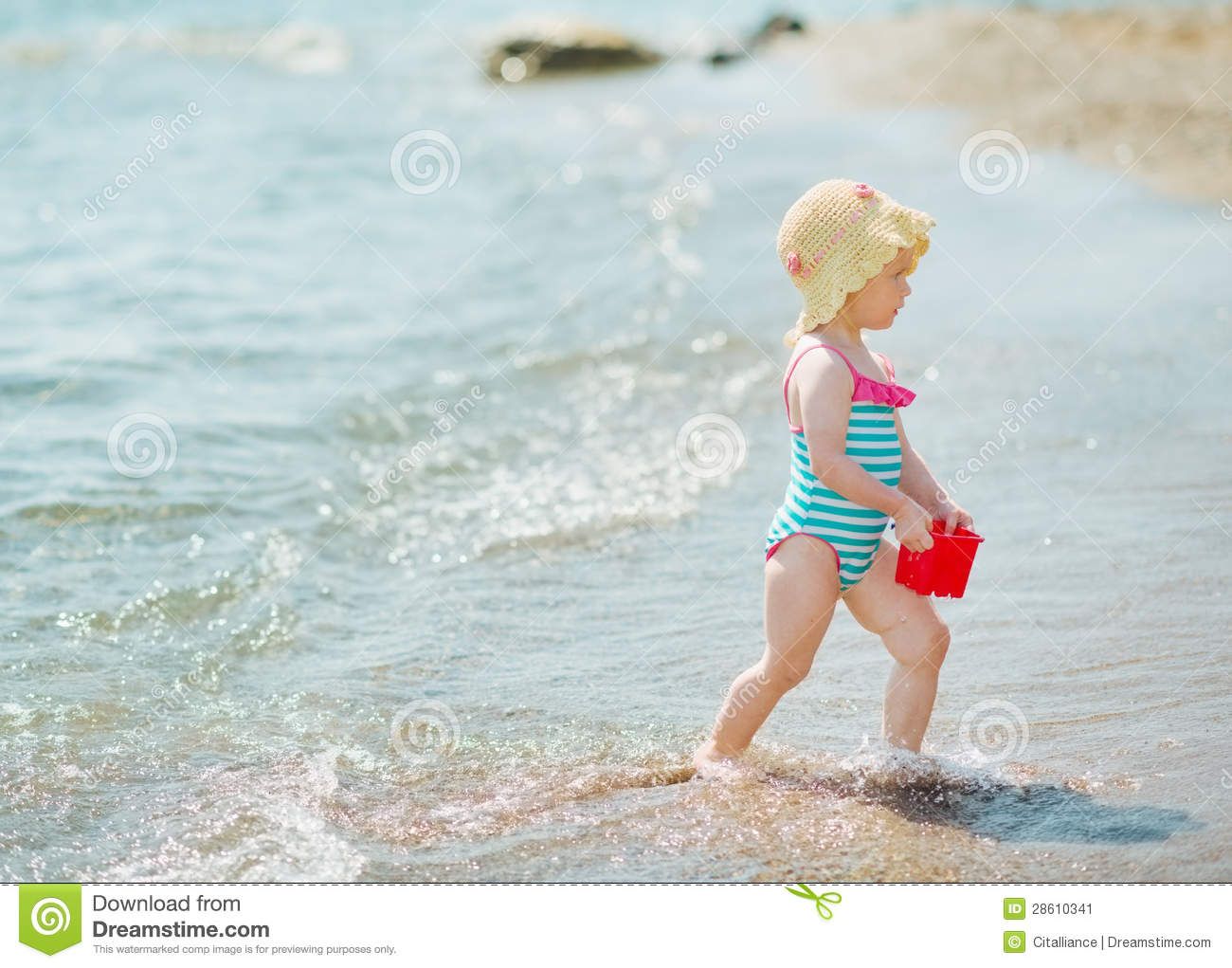 Baby playing with pail on seashore