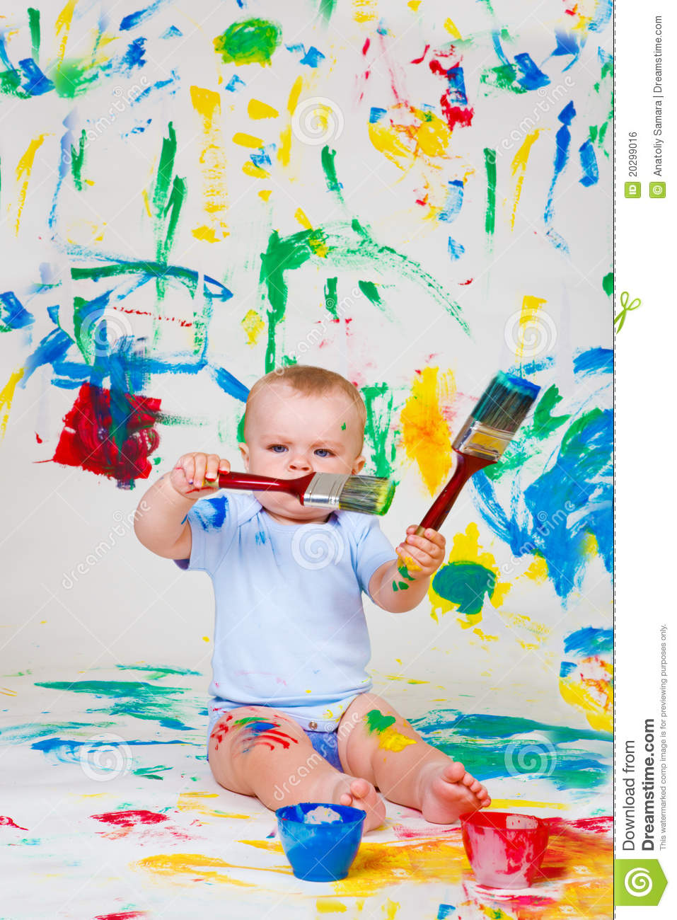 Baby playing with paintbrushes