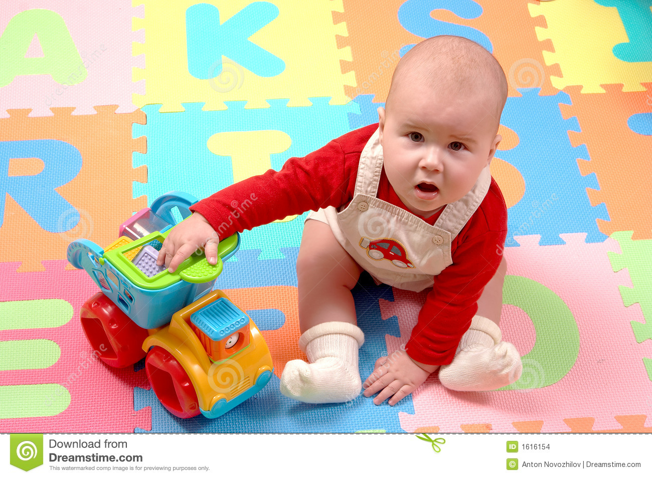 Baby plays with toy car on colourful puzzle tiles