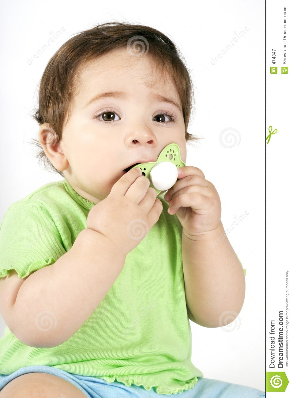 Baby putting a dummy into mouth royalty free stock photography image