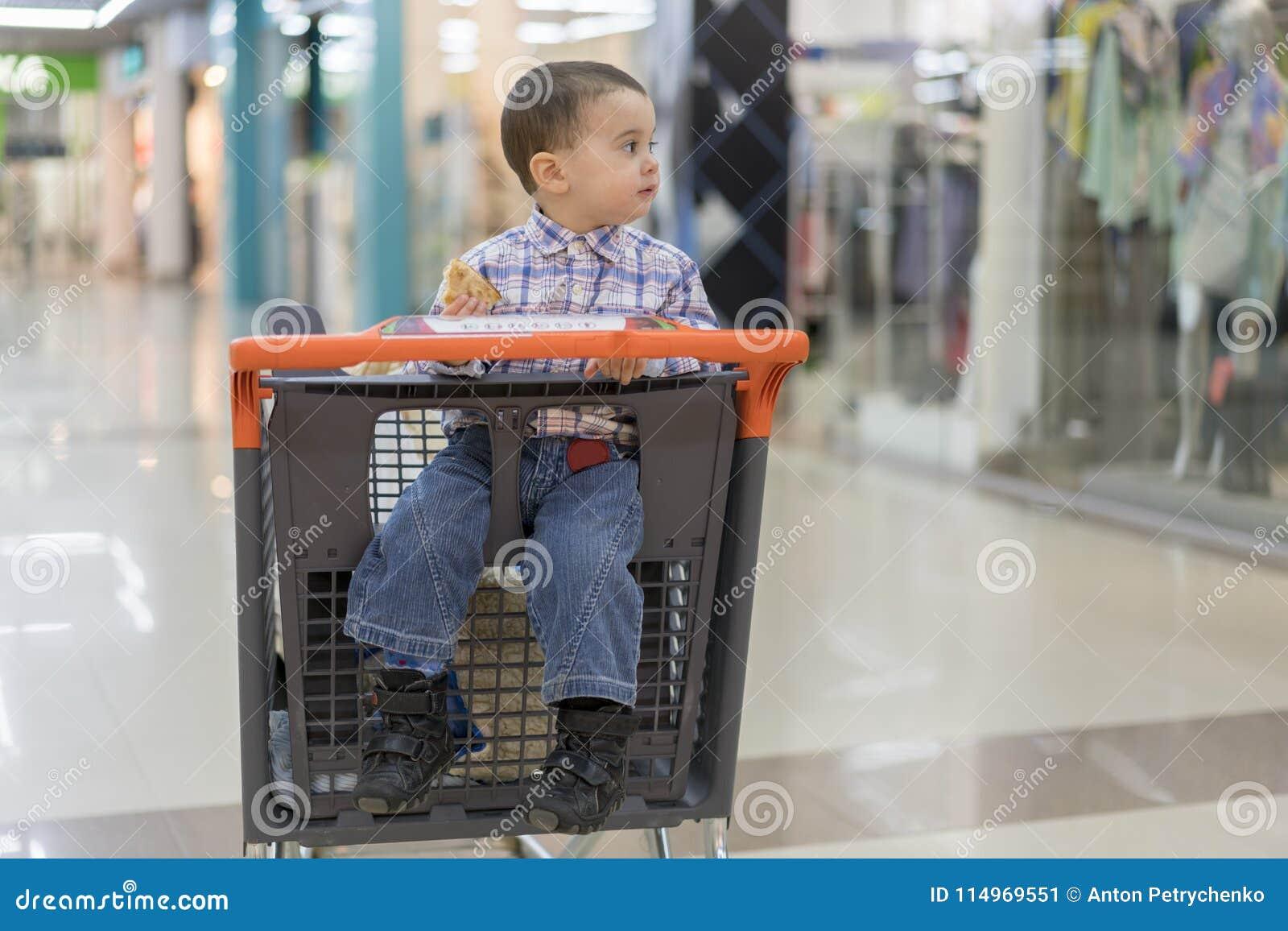 Baby reitet in eine Laufkatze durch ein Einkaufszentrum