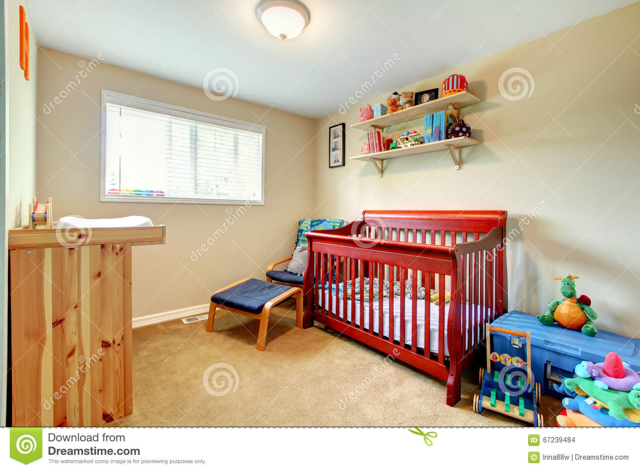 Baby room with red stained wood crib and bright interior.