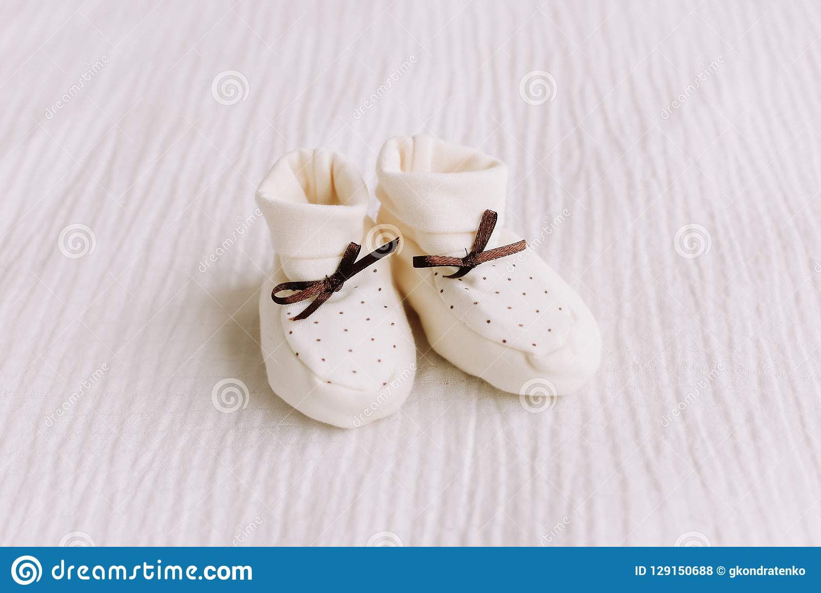 Baby`s boots on white background. Waiting for baby. white shoes for newborn on a pastel blue background.
