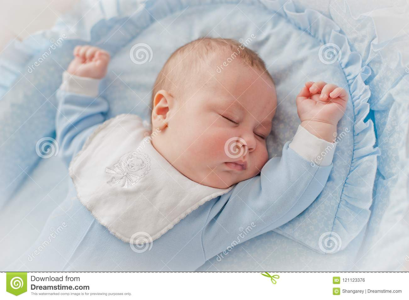 Baby`s restful sleep. Newborn baby in a wooden crib. The baby sleeps in the bedside cradle.