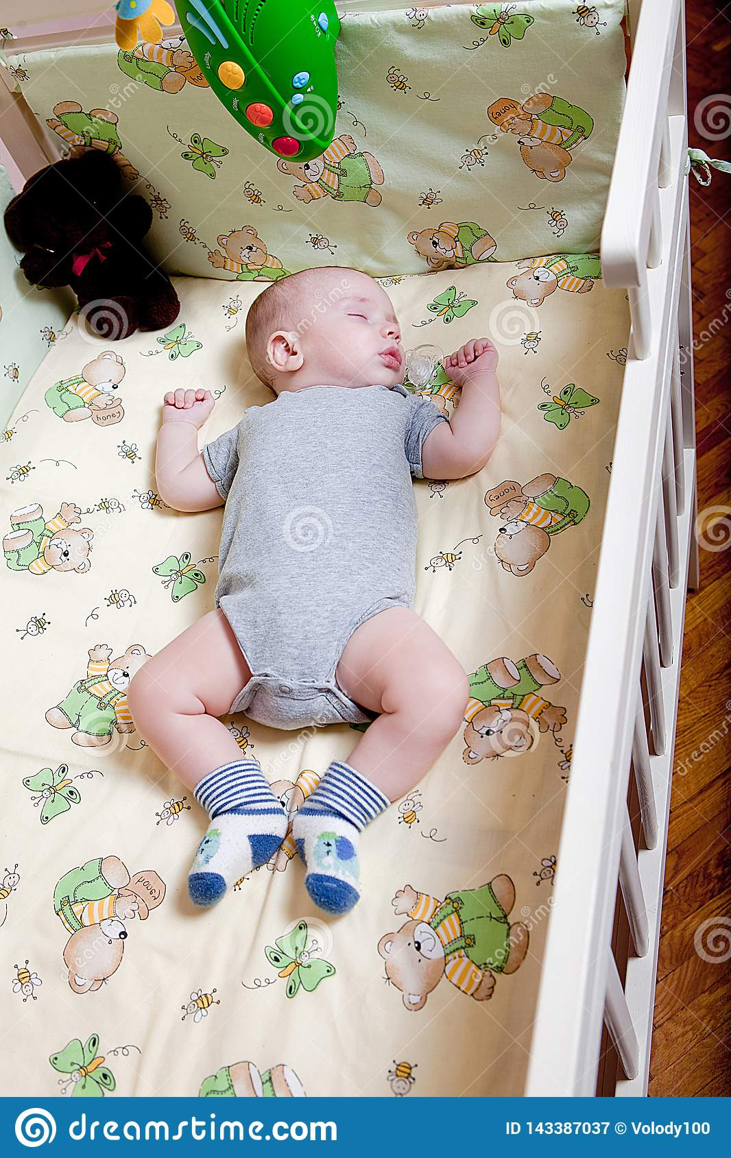 Baby`s restful sleep. Newborn baby in a wooden crib. The baby sleeps in the bedside cradle. Safe living together in a bedside cot