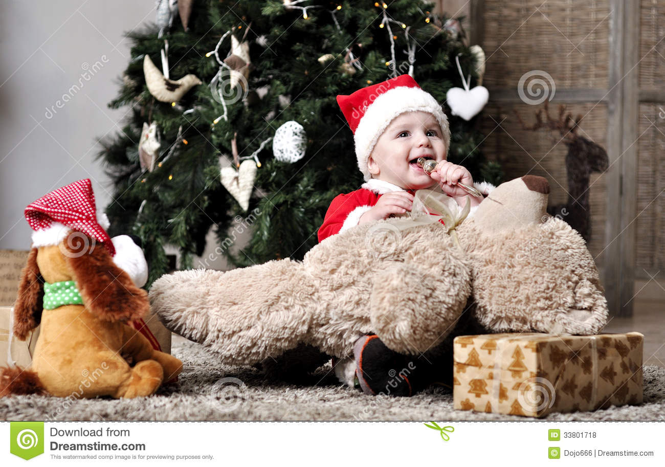 Baby in santa costume sit near decorating christma stock for Baby christmas tree decoration