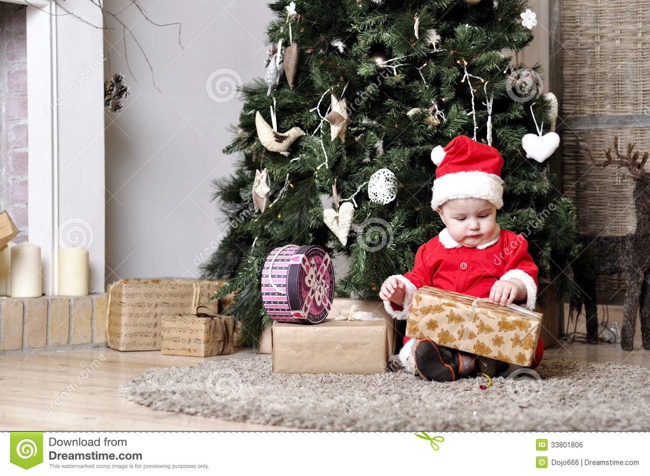 Baby in santa costume sit near decorating christmas tree for Baby christmas tree decoration