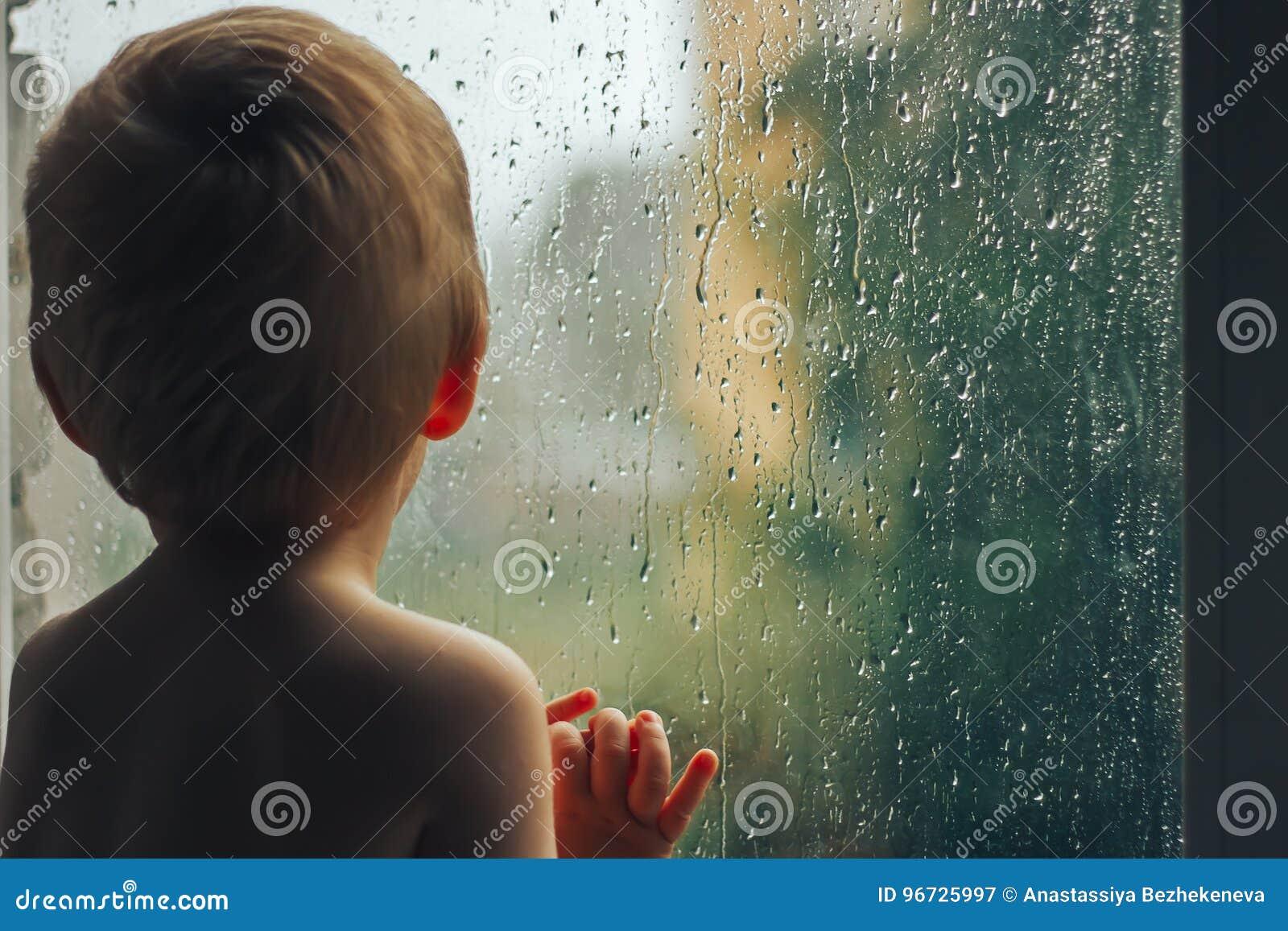Baby ser för att regna till och med fönsteranseendet med baksida