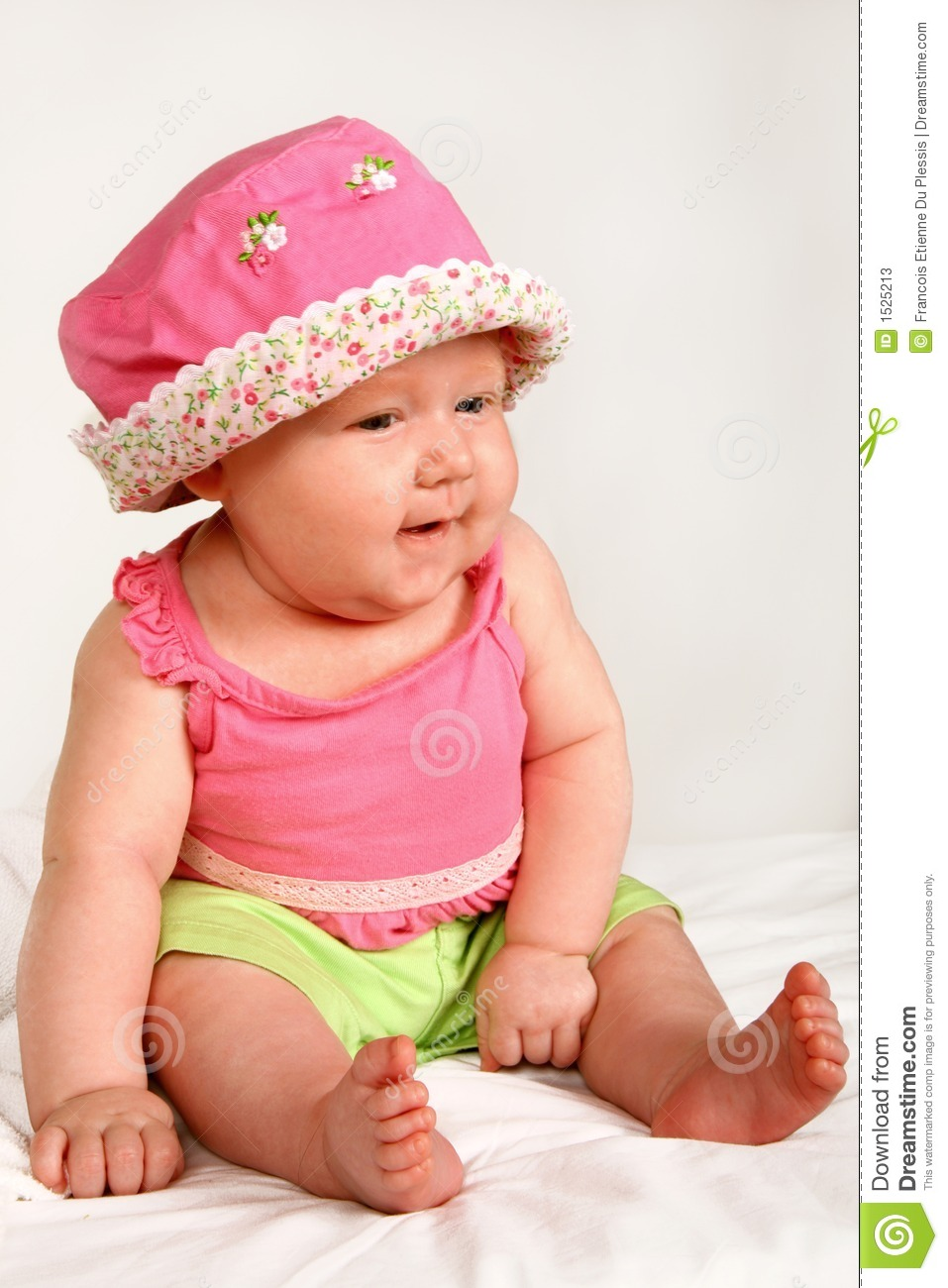 baby girl sitting with a hat on her head.
