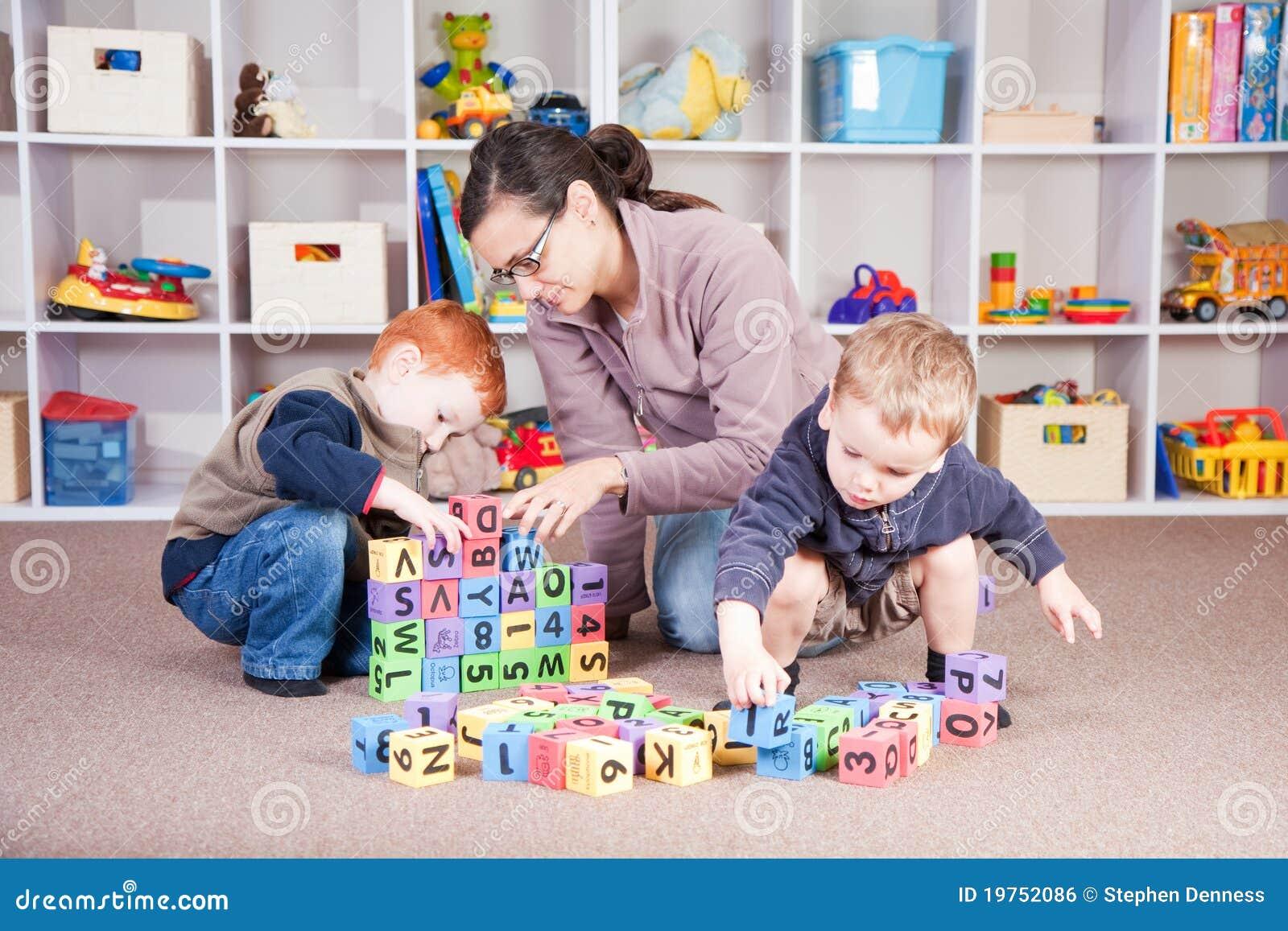 Baby-sitter que joga o jogo do bloco dos miúdos com crianças