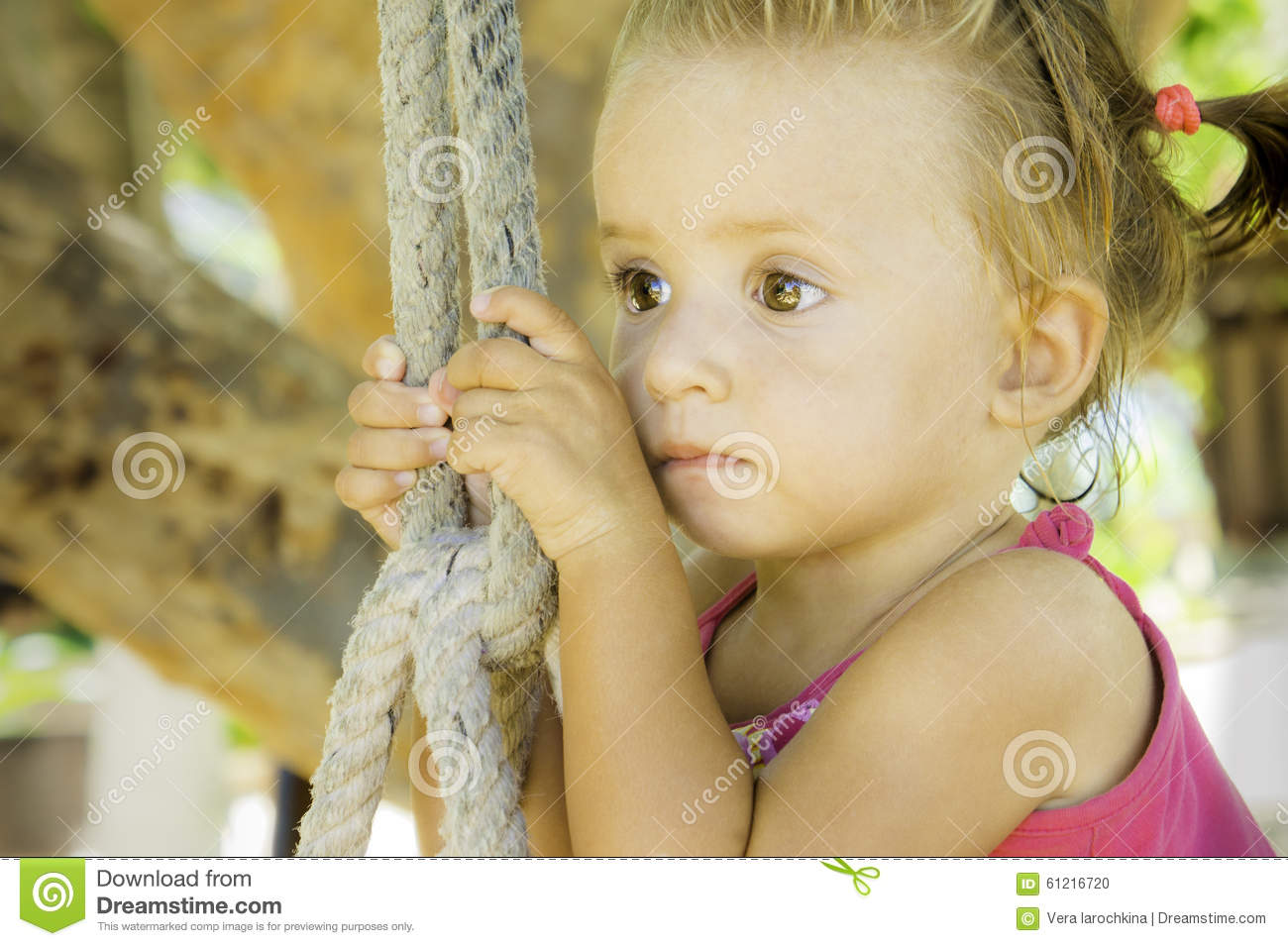 Baby sitting on swing and looking off into the distance.she has very beautiful eyes