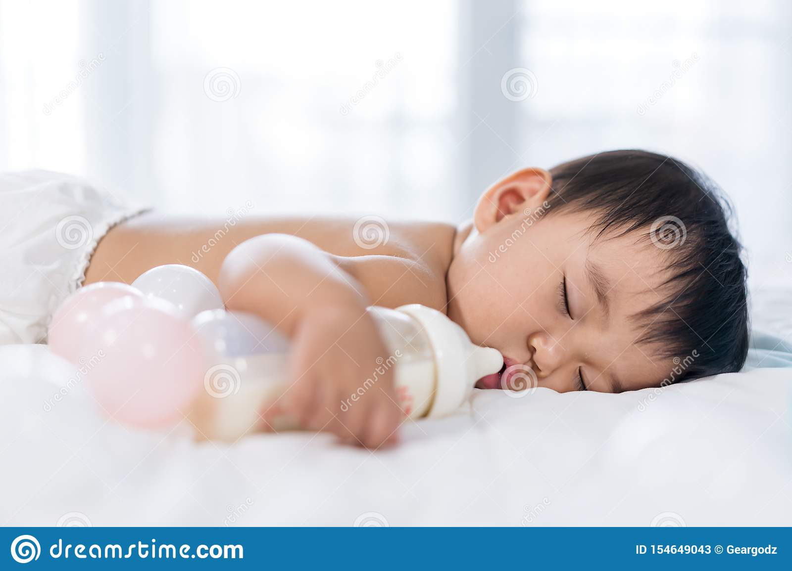 Baby Sleeping On Bed After Drinking Bottle Milk Stock Image