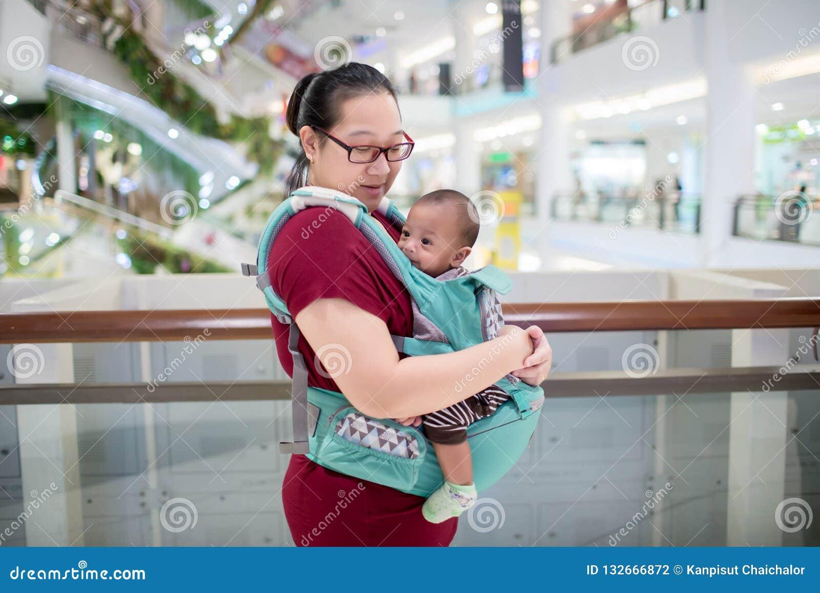 Baby in slinger binnen Weinig babyjongen en haar moeder die in warenhuis lopen