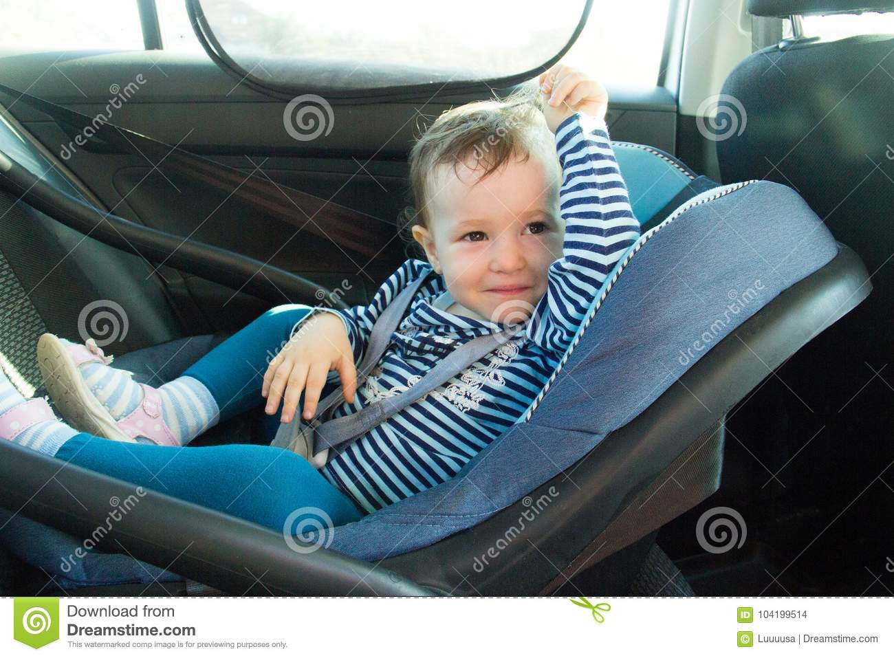 Baby smile in a safety car seat. Safety and security. one year old child girl in blue wear sit on auto cradle. Rules for the Safe