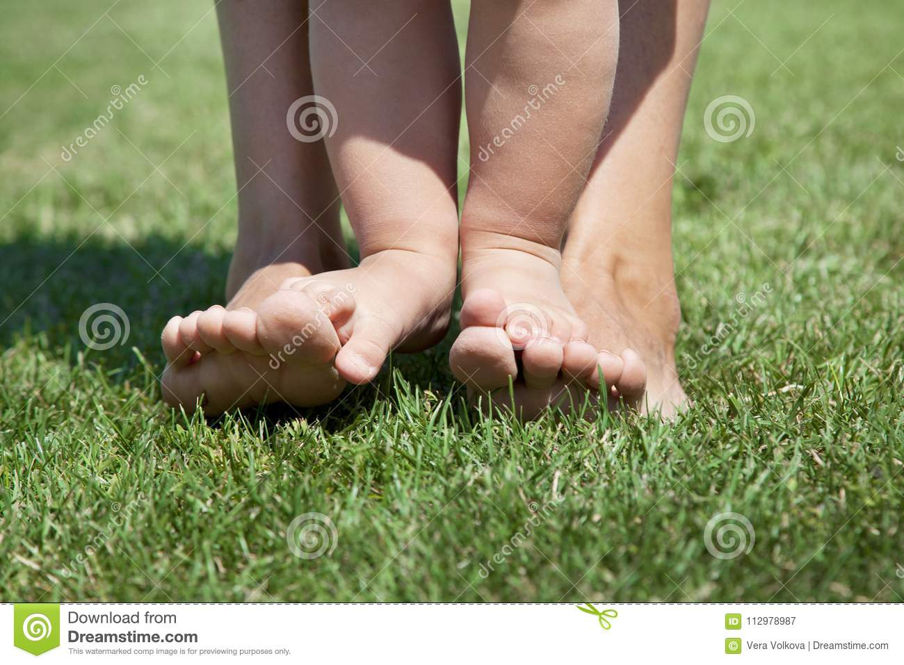 Kid standing on her mother`s legs. Standing on the green grass