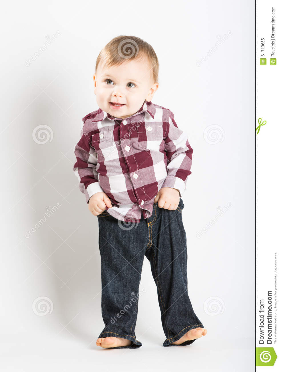 Baby Stands In Flannel And Jeans Pulling Up Pants Stock