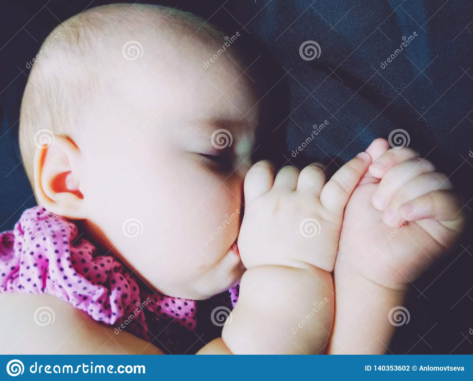 The baby sucks a thumb in a sleep
