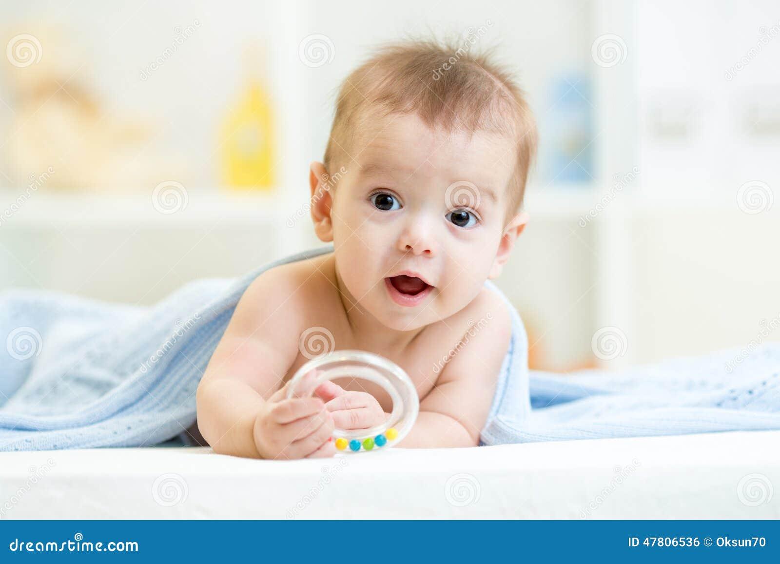 Baby with teether under blanket indoor