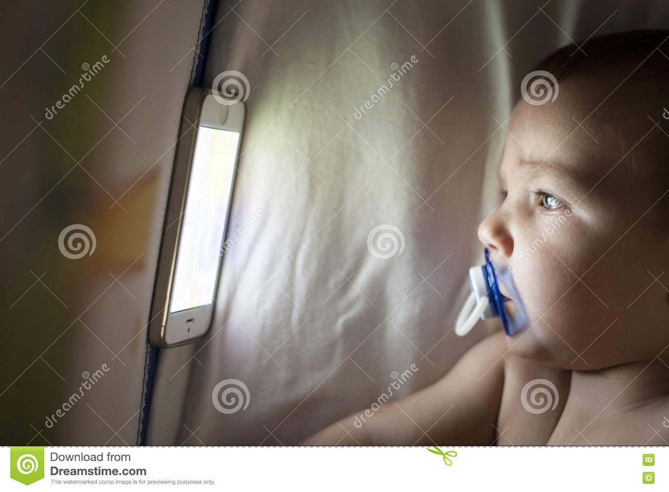 Baby watching a lullaby cartoons with mobile phone on the crib