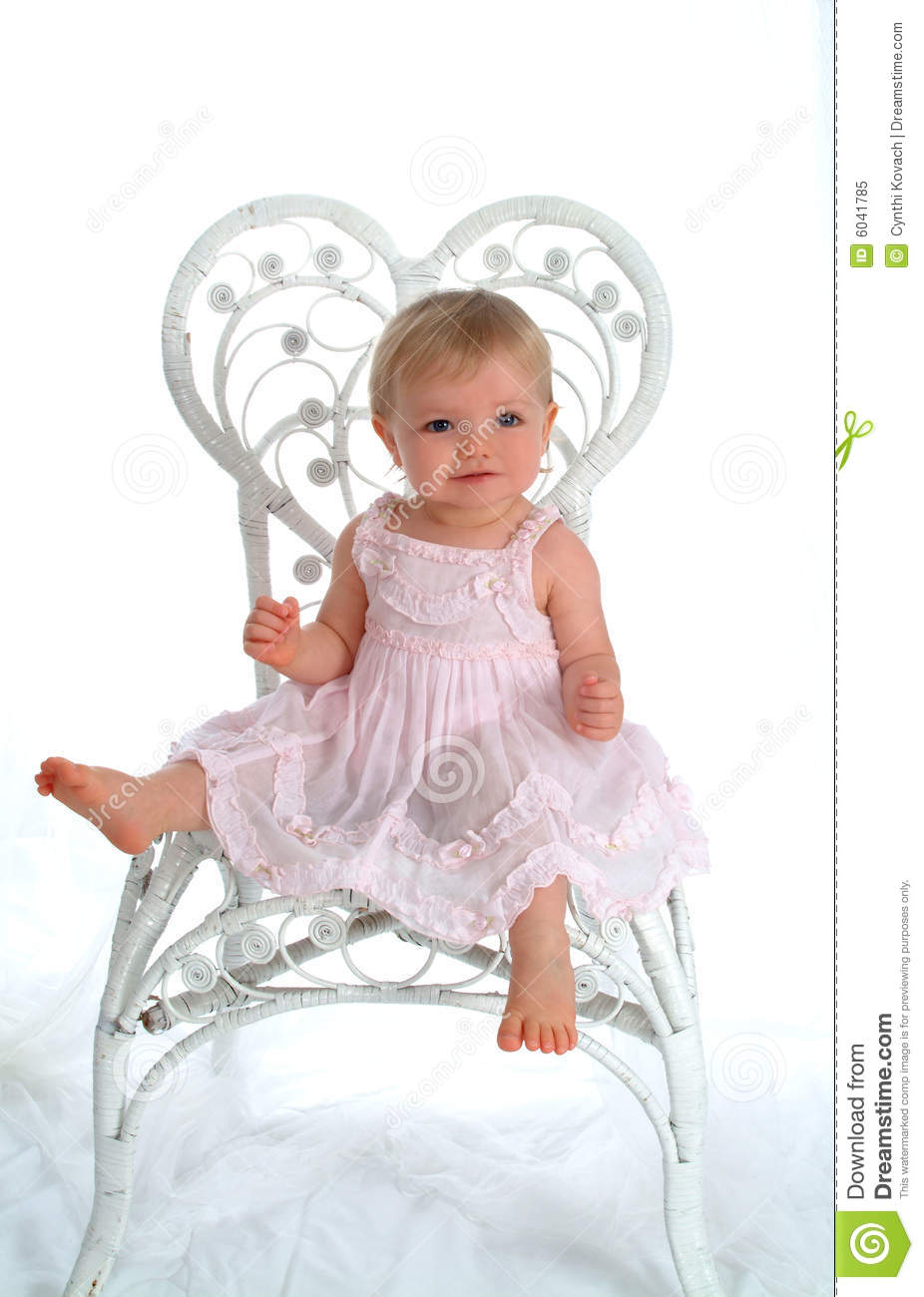 Baby in white wicker chair stock photography for White toddler chair
