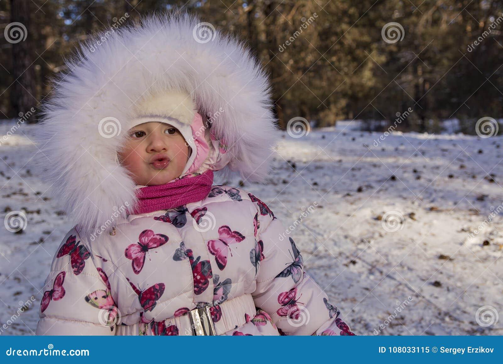 Baby am Winter Durchbrennenschnee der jungen, schönen Frau in Richtung zur Kamera auf Winterhintergrund