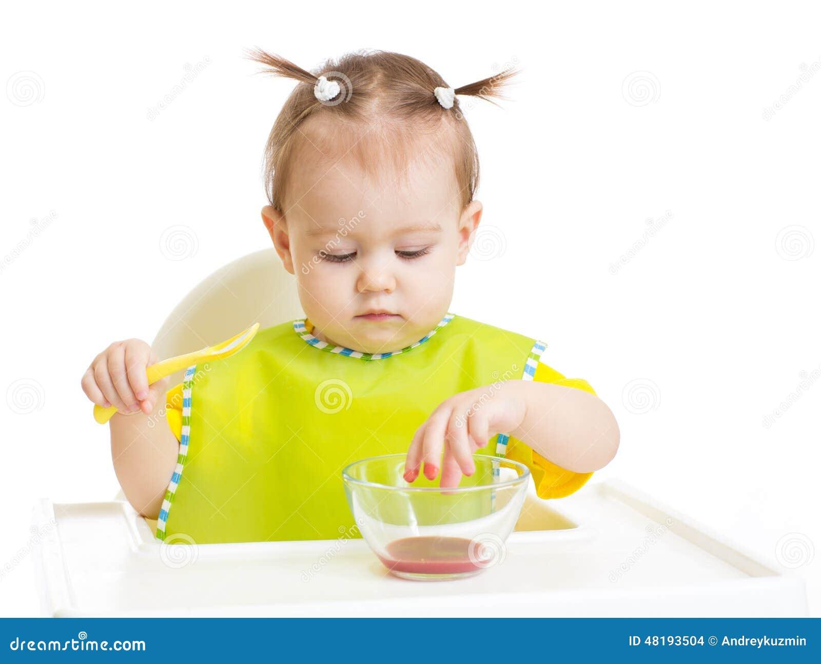 Babyessen und gesetzte Finger in das Lebensmittel, das an sitzt