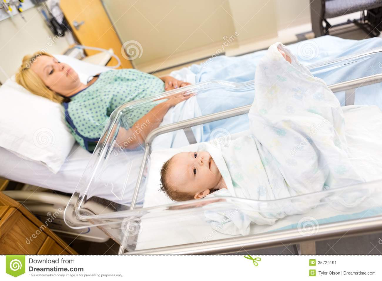 Babygirl Lying In Bassinet With Woman On Hospital Stock