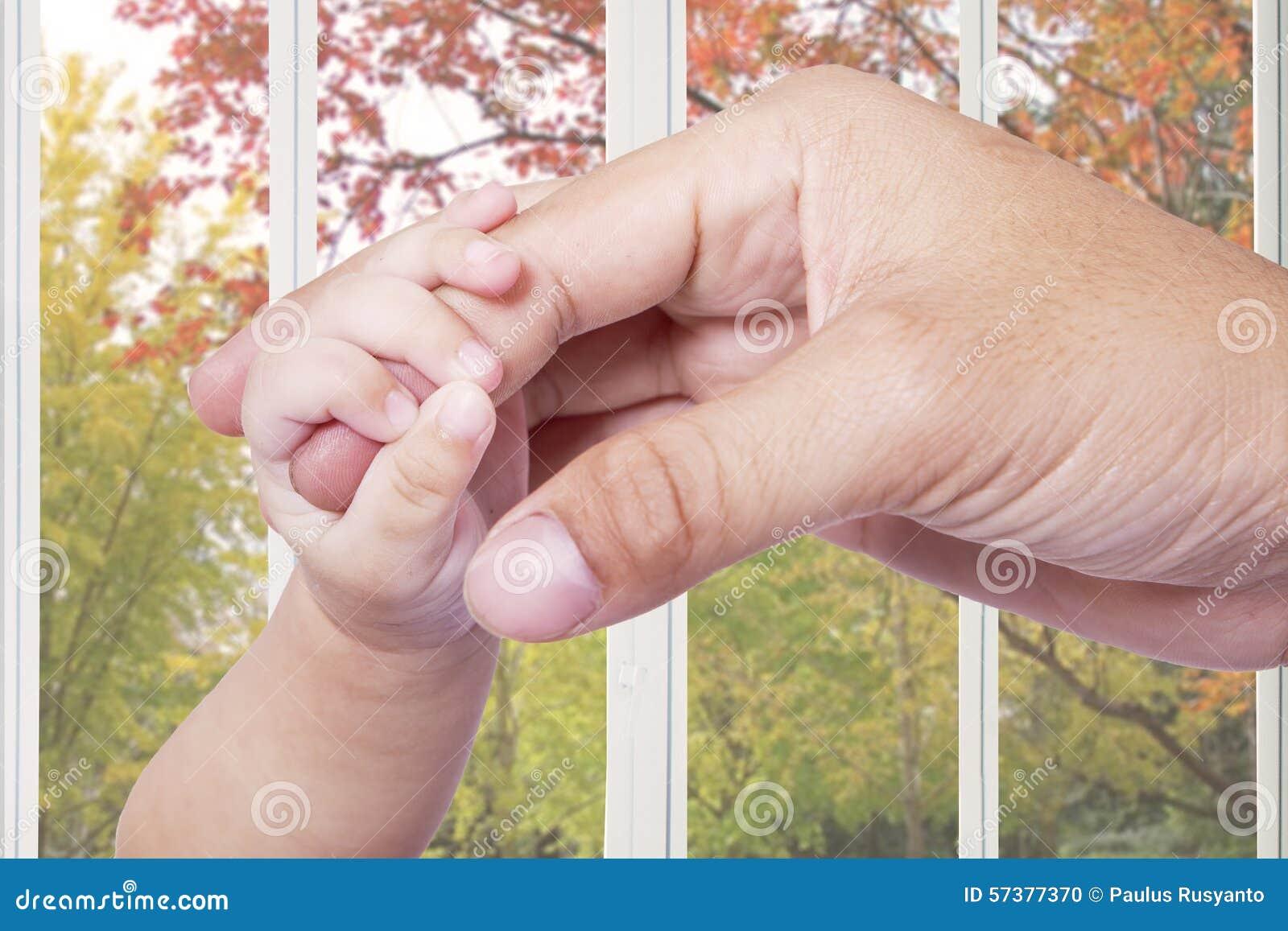 Babyhand die de vadervinger grijpen