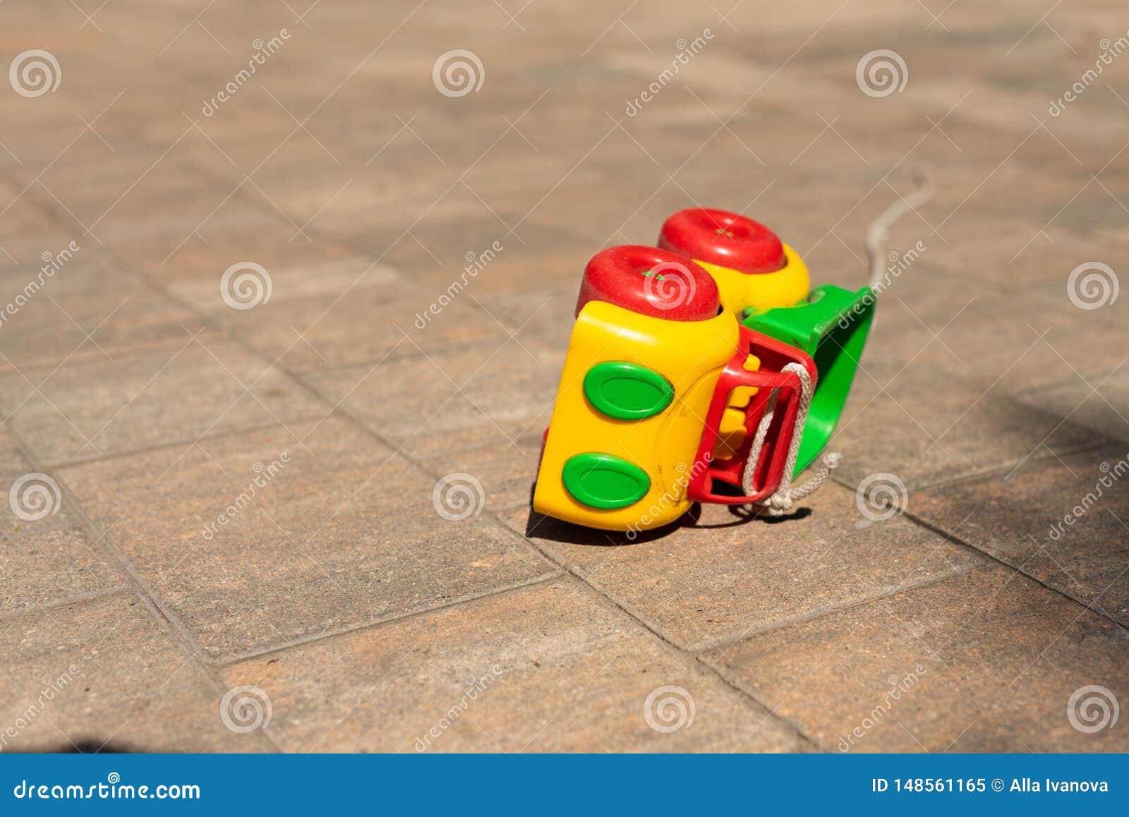 Babykinder spielen Hintergrund: Spielzeug farbiges Auto klopfte vorbei auf dem Pflasterstein