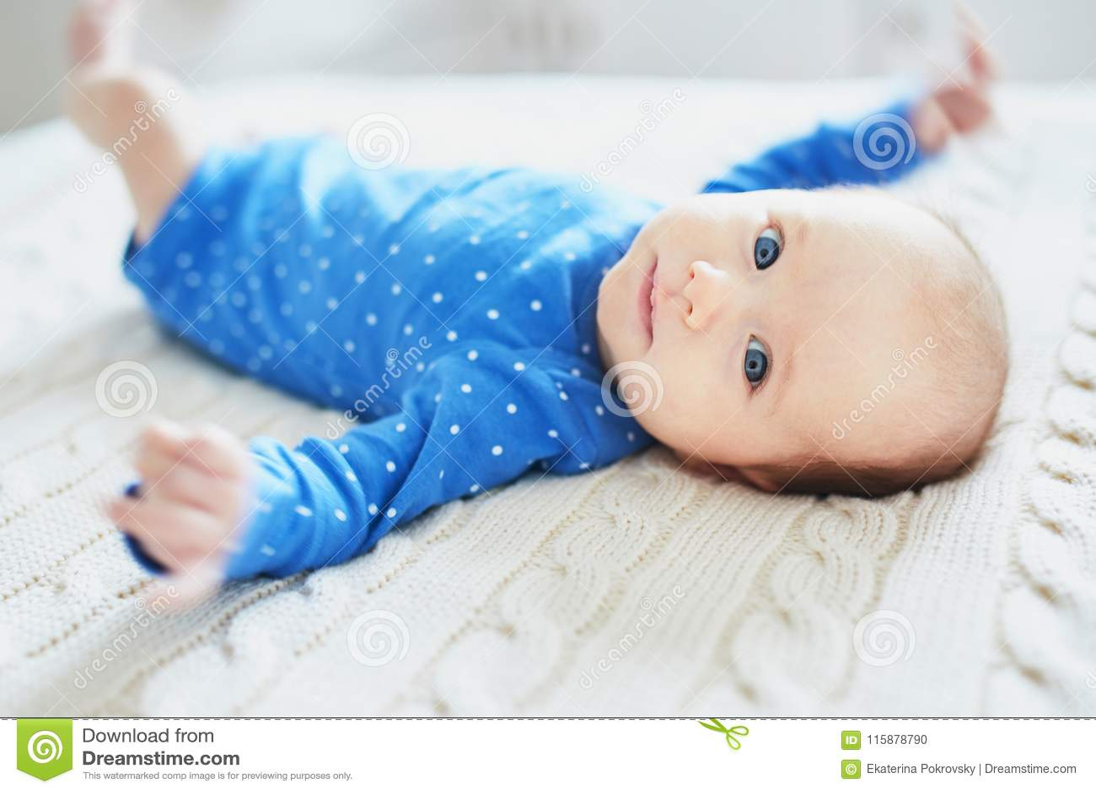 Babymeisje die blauwe kleren dragen die in slaapkamer ontspannen
