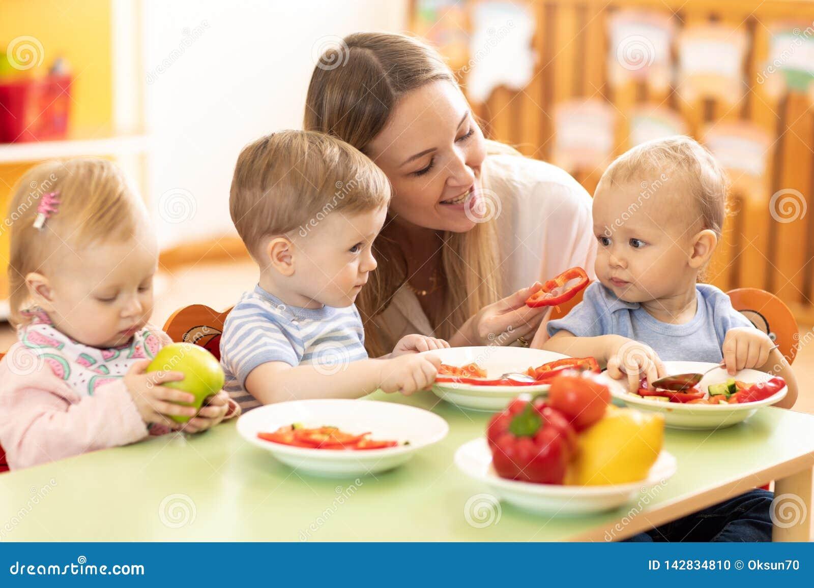 Babysitter feeding nursery babies. Toddlers eat healthy food in daycare